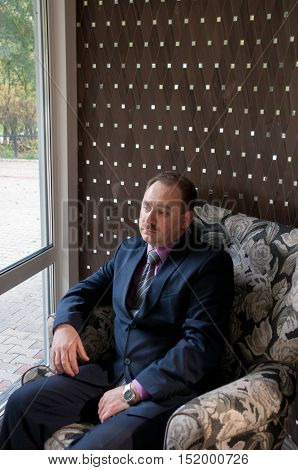 Man in suit sitting in an armchair near the window