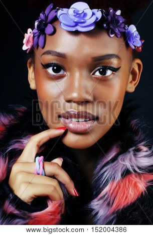 young pretty african american woman in spotted fur coat and flowers jewelry on head smiling sweet etnic make up bright fashion close up