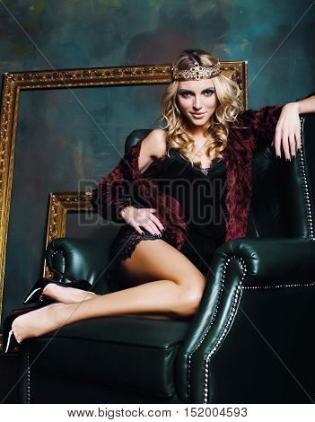 young blond woman wearing crown in fairy luxury interior with empty antique frames total wealth long legs, lifestyle rich people concept close up