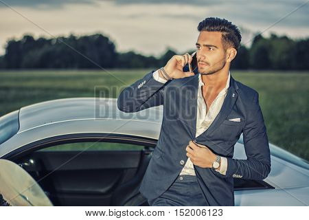 Portrait of young attractiave man in business suit sitting in his new stylish car outdoor in countryside