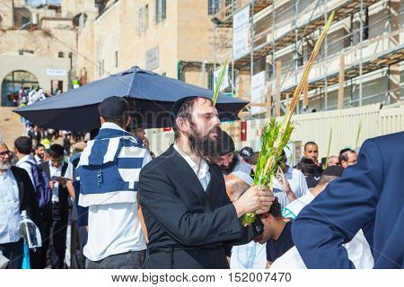 JERUSALEM, ISRAEL - OCTOBER 12, 2014: The area in front of Western Wall of Temple filled with people. Jews wearing tallit hold ritual plants. Sukkot, Blessing of the Kohanim