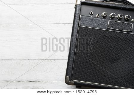 Guitar amplifier on white wood table, top view