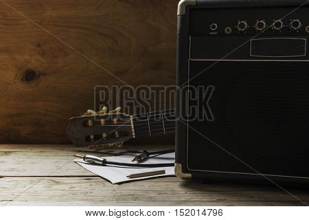 Guitar amplifier and guitar on wood table light and shadow