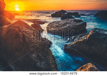 Sunset on the coast of the Sri Lanka at dawn with rocks in foreground. Beauty world