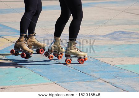 Two women with matching roller skates and black leggings roll across a colorful sidewalk.