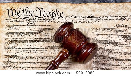 Wooden gavel on top of American Bill of Rights document We the People.