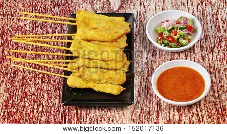Charcoal boiled pork satay, home made in big size, served with Thai cucumber chili sauce as