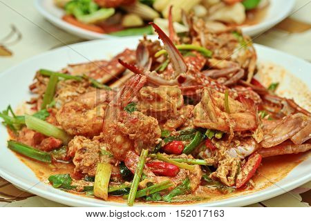 Close up of stir-fried crab and shrimp in curry power is top-ten of popular Thai food as seafood to fried with  fresh milk ,grill curry ,egg ,oyster oil and yellow curry power. Selective focus.