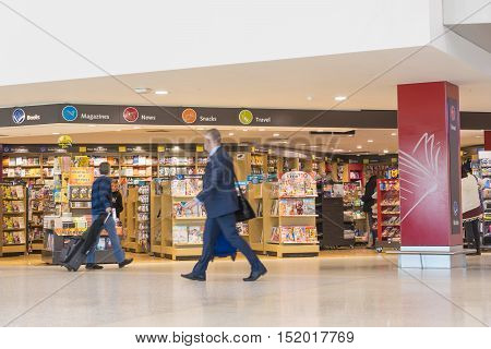 Melbourne, Australia - September 20, 2016: View of businessman passing by a duty free bookshop selling books, news, magazines, gifts and snacks at Melbourne airport.