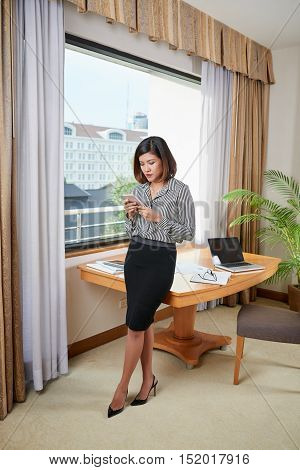Filipina business lady reading messages on her smartphone