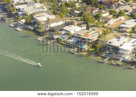 Gold Coast, Australia - September 22, 2016: Aerial view of luxury, waterfront houses with swimming pools and docks and boats in Gold Coast during sunset.