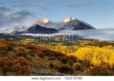 Sunrise at Twin mountain View of Mount Sopris and Mount Elk with Fall color and morning mist Snowmass Maroon Bells Wilderness area Colorado
