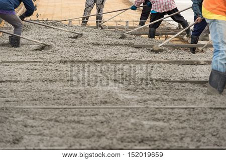 Construction workers are using the newly poured cement spreaders into the ground to allow ordinary cement concrete with a thickness determined by the engineer.