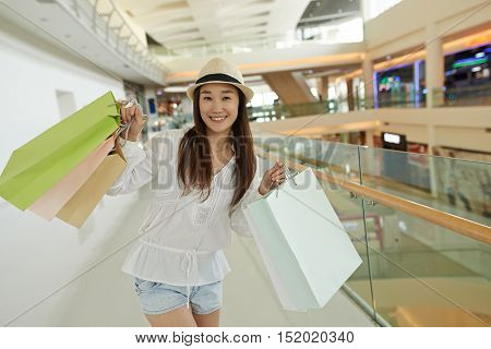 Portrait of happy Korean young woman with paper-bags standing in mall