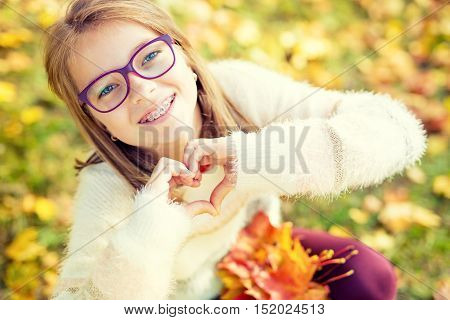 Smiling little girl with braces and glasses showing heart with hands.Autum time.