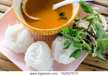 (Kanom jeen) Noodles and Chicken curry with vegetable on wood background Food collection in ThialandRice Noodles in sweet curry sauce/ Traditional Thai cuisine rice vermicelli served with boiled egg sweet peanut sauce and vegetable on wood table.Selective