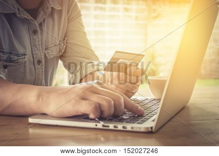 Online payment. Man's hands holding a credit card and using laptop for online shopping with vintage filter effect