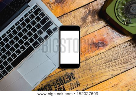 smart phone over laptop with Retro rotary telephone on wood desk. Smartphone with blank screen and can be add your texts or others on smartphone.