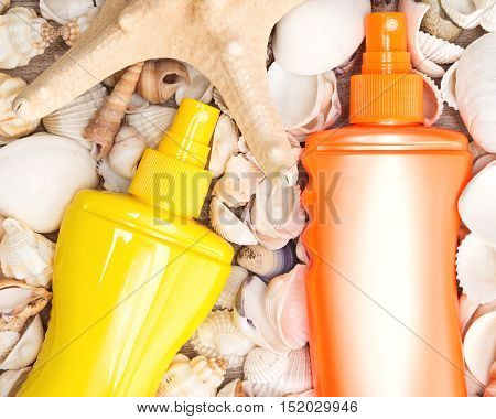 Close-up of yellow and orange containers of cosmetic sunscreen products with various shells and starfish. Concept of skin care cosmetics containing sun protection factor for beach vacation