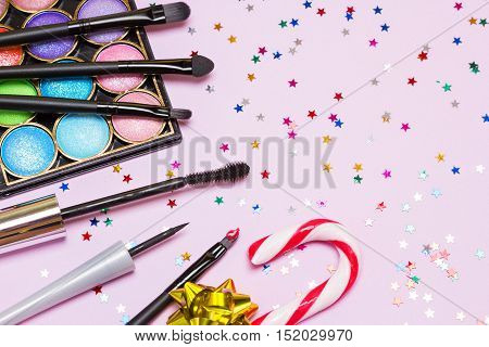 Makeup for festive party. Red lipstick, black eyeliner, mascara, bright color glitter eyeshadow, brushes and applicator with candy cane, gift wrap bow and confetti on pink background. Copy space