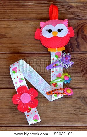 Original organizer for hairpins, a felt owl, a set of barrettes. Kids crafts. Brown wooden background