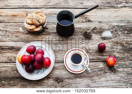 Inspirational early morning breakfast in country, flat lay. Top view on old rustic wooden table with fresh coffee in cup and pot, tasty plums and cookies.