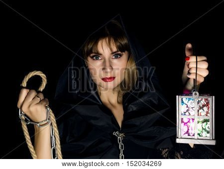 mysterious young woman holding rope and old flashlight. on a dark background.