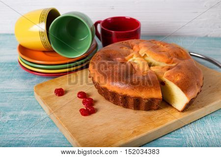 Home-made biscuit pie red berries and cups. Pie on a wooden board is cut off a piece of pie a row has scattered several dried berries on a background red and green tea ceramic cups