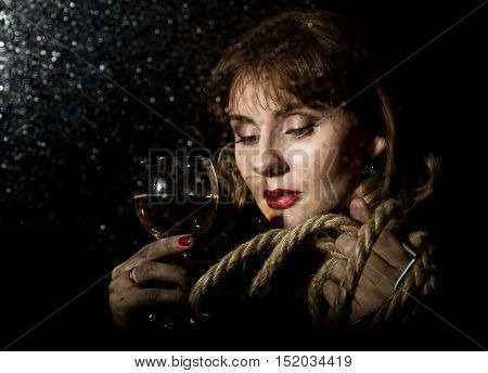 mysterious young woman with a glass of wine posing behind transparent glass covered by water drops. on a dark background.