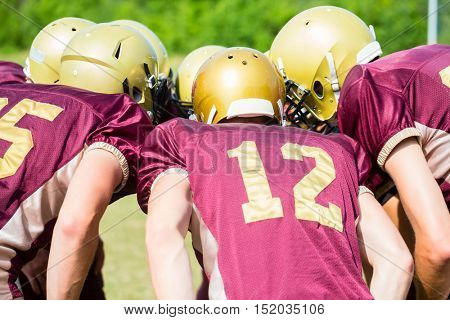 American Football players at strategy huddle
