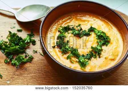 smashed pumpkin soup close up photo with parsley heart and spoon