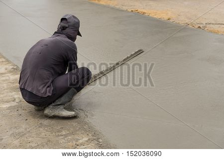 Workman finishes and smooths concrete surface on new road.