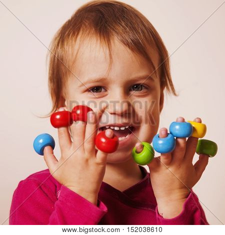 cute little girl laughing and playing with colored toys