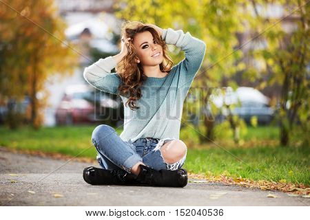 Happy young woman with long curly hairs sitting on city street. Fashion model in ripped jeans outdoor