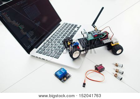 Diy rc car with components on laptop. Workplace of electronic inventor with constructed toy, wireless transceivers, servo and rey module near computer
