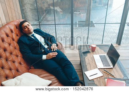 Tired office worker with eyes closed lying on leather sofa. Working day, fatigue and daily routine concept.