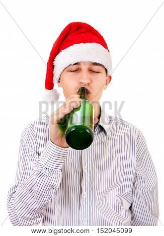 Young Man in Santa Hat drinks a Beer on the White Background