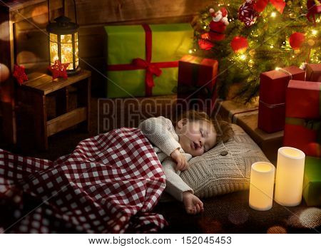 Merry Christmas and Happy Holiday! Cute little child baby girl sleeping near Christmas tree.
