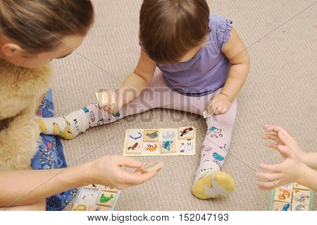 Daddy and kids playing children's lotto with figures of animals