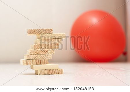 Balance concept with wooden planks on the table with red ball on the background