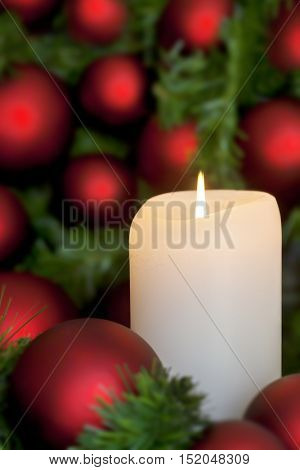 Christmas candle with red baubles, over black background.