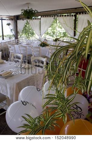 FLORENCE, ITALY - MAY 21 2016: Florentine restaurant set up for a wedding with balloons and a plant in the foreground