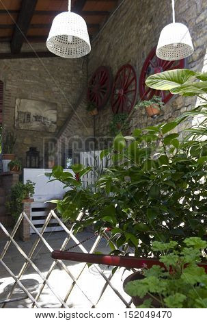 FLORENCE, ITALY - MAY 21 2016: Outdoors of a old style restaurant on Florentine hills Italy with white hanging lamps and vintage wheels