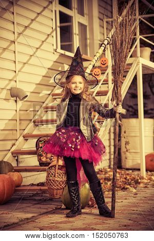 Pretty little girl in a costume of witch with her magic broom celebrating halloween. Trick or treat. Halloween party.