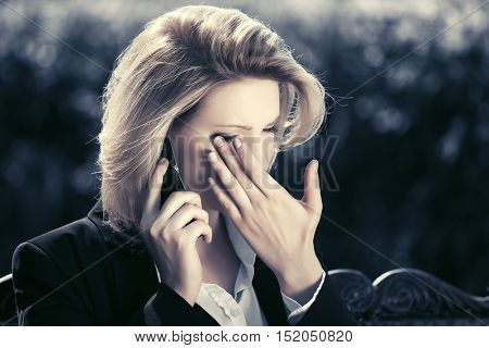 Sad business woman calling on cell phone on city street