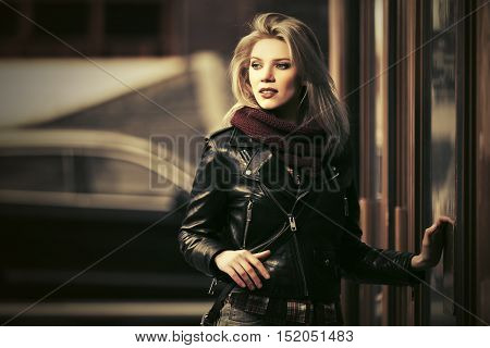 Young blond woman in leather jacket on city street. Stylish fashion model outdoor