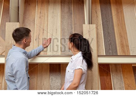 Couple looking at parquet board for home flooring in store, in home improvement warehouse exterior