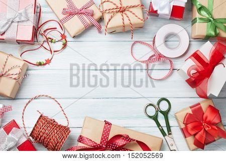 Christmas background with gift boxes on wooden table. Top view with copy space. Gift wrapping