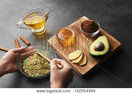 Female hands making nourishing facial mask with natural ingredients on grey background