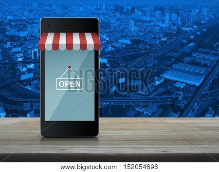 Modern smart mobile phone with on line shopping store graphic and open sign on wooden table over city tower and expressway